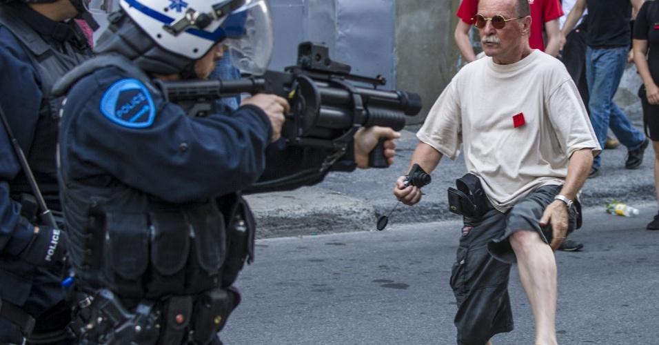 22.jul.2012 - Polícia aponta arma para manifestante durante protesto pedindo melhorias na educação e contra o aumento das taxas universitárias, em Montreal, no Canadá