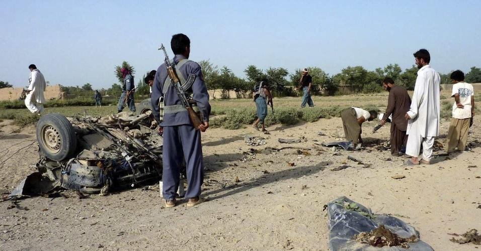 22.jul.2012 - Policiais e curiosos observam restos de um veículo que explodiu em Kunduz, no Afeganistão. Pelo menos quatro pessoas morreram no ataque