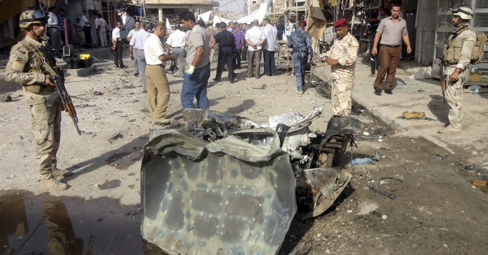 22.jul.2012 - Policiais iraquianos inspecionam destroços de carro-bomba que explodiu neste domingo (22), em um mercado em Najaf, Iraque