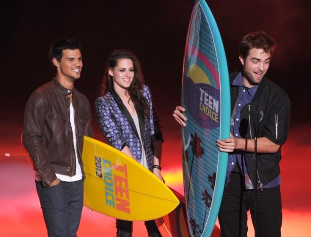 "Empunhando o prêmio ""Ultimate Choice Award"", Taylor Lautner, Kristen Stewart e Robert Pattinson participaram da premiação do canal Boomerang ""Teen Choice Awards"" (22/7/12) - Getty Images"