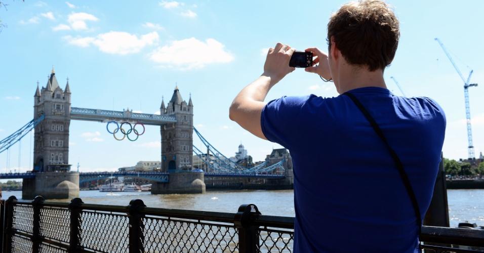Turista fotografa a Tower Brigde em Londres; cartão postal da cidade-sede das Olimpíadas 2012 está decorado com os anéis olímpicos (22/07/2012)
