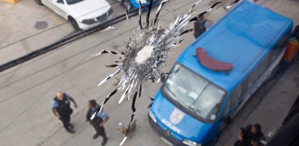 Imagem mostra vidro destruído após ataque contra a UPP Nova Brasília, no Complexo do Alemão, em 2012. Durante a ação criminosa, uma policial militar foi atingida por um disparo de fuzil e morreu