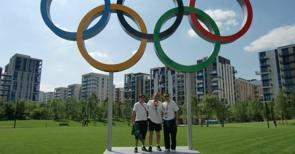 Esgrimista Renzo Agresta e sua equipe posam em frente aos aros olímpicos