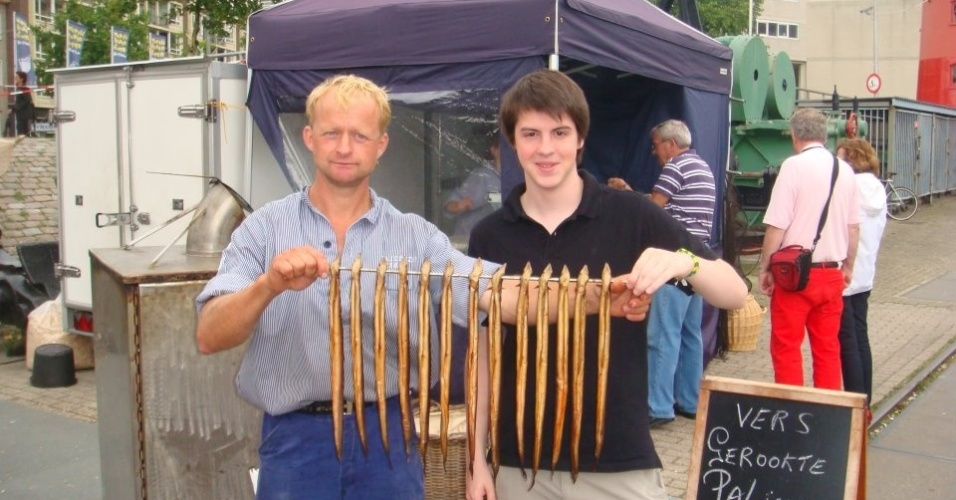 Felipe Ugolini, 18, mostra um peixe tradicional da Holanda que é vendido em barracas na rua.