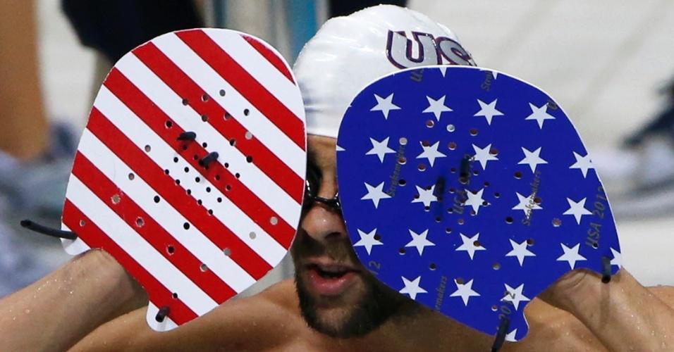 Michael Phelps tenta remover seus óculos de natação enquanto usa equipamento nas cores da bandeira dos EUA (24/07/2012)