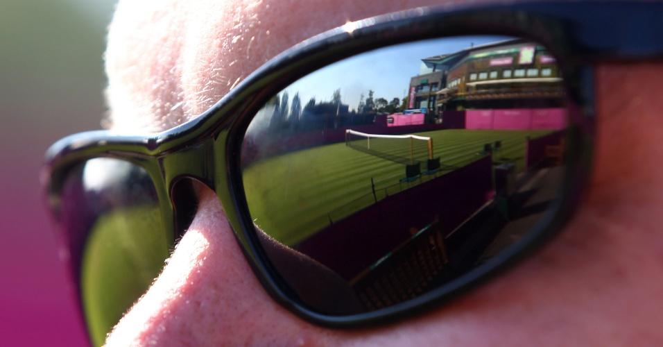 Quadra de Wimbledon, onde o torneio de tênis olímpico será disputado, é vista refletida em óculos de membro da organização das Olimpíadas (24/07)