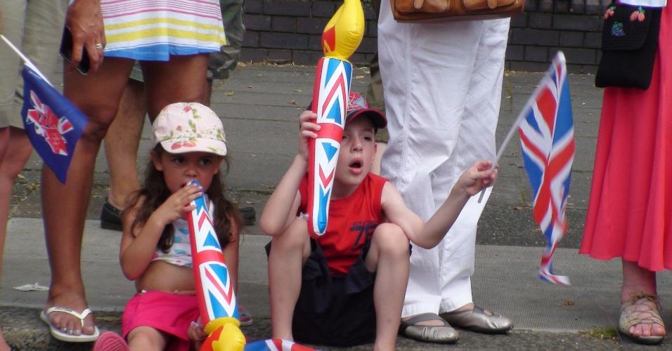 Crianças brincam na calçada à espera da passagem da tocha olímpica pelo bairro de Enfield (25/07/2012)
