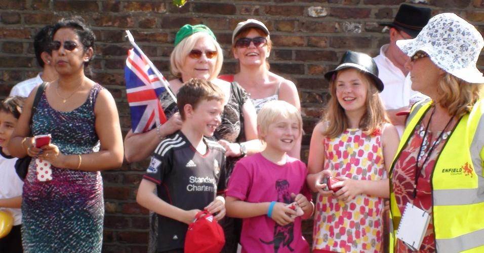 Família segura bandeiras britânicas, à espera da passagem da tocha olímpica (25/07/2012)