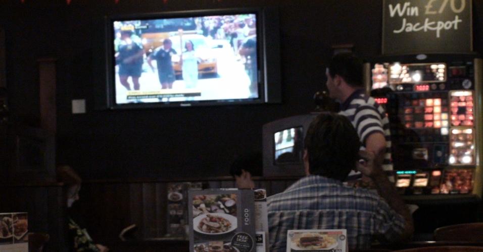 Moradores de Enfield acompanham pela TV o trajeto da tocha antes dela chegar ao borough londrino (25/07/2012)