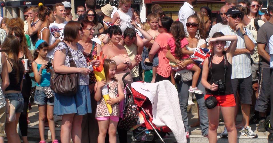 Público se aglomera esperando a passagem da tocha olímpica por Enfield, ao norte de Londres (25/07/2012)