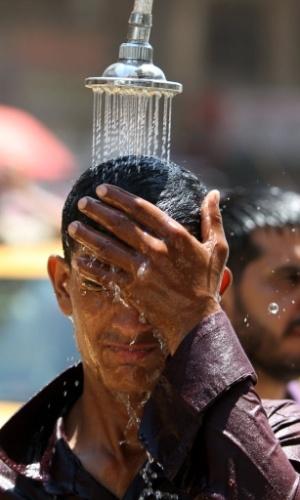 26.jul.2012 - IIraquiano se refresca em chuveiro  para suportar o calor de 48°C, em Bagdá, no Iraque. As ruas da cidade ganharam chuveiros para amenizar a onda de calor na região