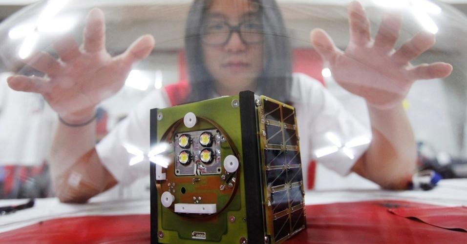 26.jul.2012 - O artista Song Ho-Jun, 34 anos, posa com seu satélite, considerado o primeiro feito por apenas uma pessoa. Com formação em Engenharia, Ho-Jun queria mostrar que pessoas comuns conseguem criar qualquer coisa com a ajuda da internet e de redes sociais. Ainda que outros aparelhos já tenham sido criados por universidades e grupos científicos, o OpenSat é o primeiro satélite concebido e financiado por apenas uma pessoa. Para colocá-lo em órbita será necessário mais de mil reais