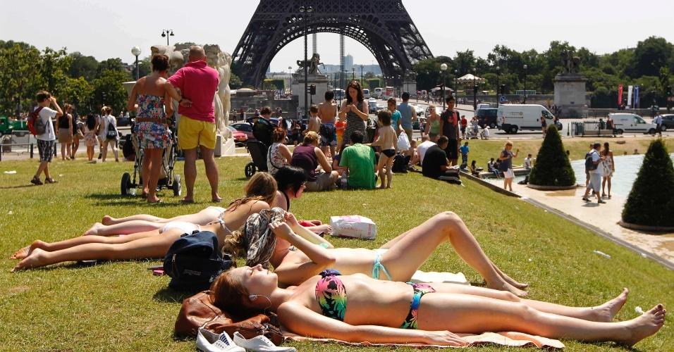 26.jul.2012 - Pessoas tomam sol nesta quinta-feira (26) no gramado em frente à torre Eiffel, em Paris, na França