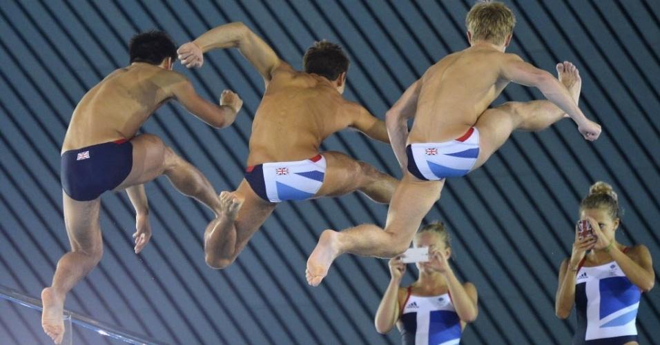 As britânicas Tonia Couch (à direita) e Sarah Barrow tiram fotos de companheiros de equipe de saltos ornamentais em treino para os Jogos de Londres