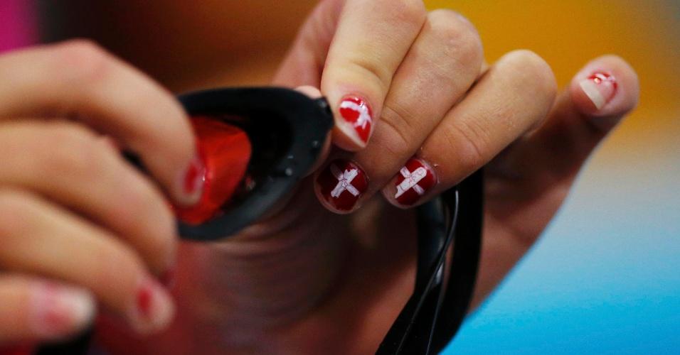 Com bandeira de seu país pintada nas unhas, nadadora dinamarquesa ajusta seus óculos antes de treino (26/07/12)