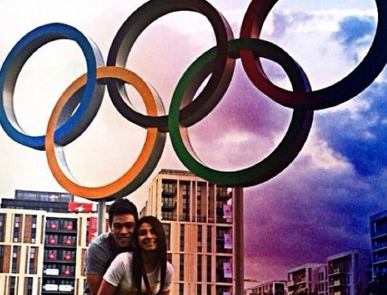 Ginastas e namorados, os brasileiros Sérgio Sasaki e Bruna Leal posam juntos sob os aros olímpicos da Vila