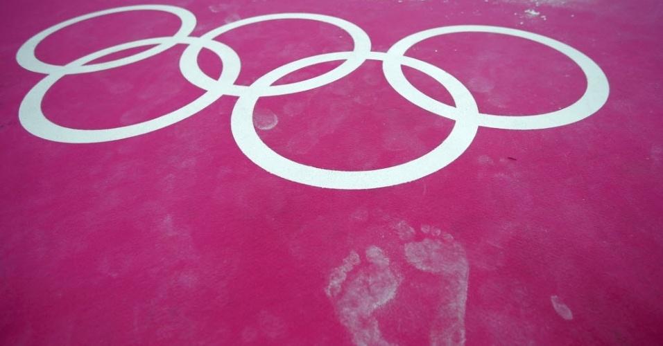 Marcas de pés aparecem perto dos anéis olímpicos em treino da ginástica nos Jogos Olímpicos de Londres