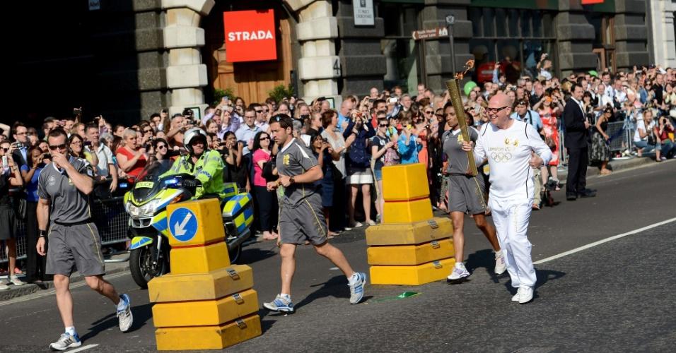 Multidão acompanha de perto passagem da tocha olímpica pelas ruas de Londres (26/07/12)