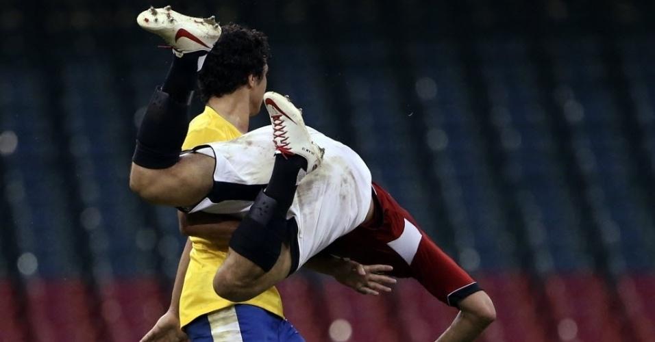 O egício Eslam Ramadan alça voo após choque com o brasileiro Rafael na estreia do futebol masculino em Londres