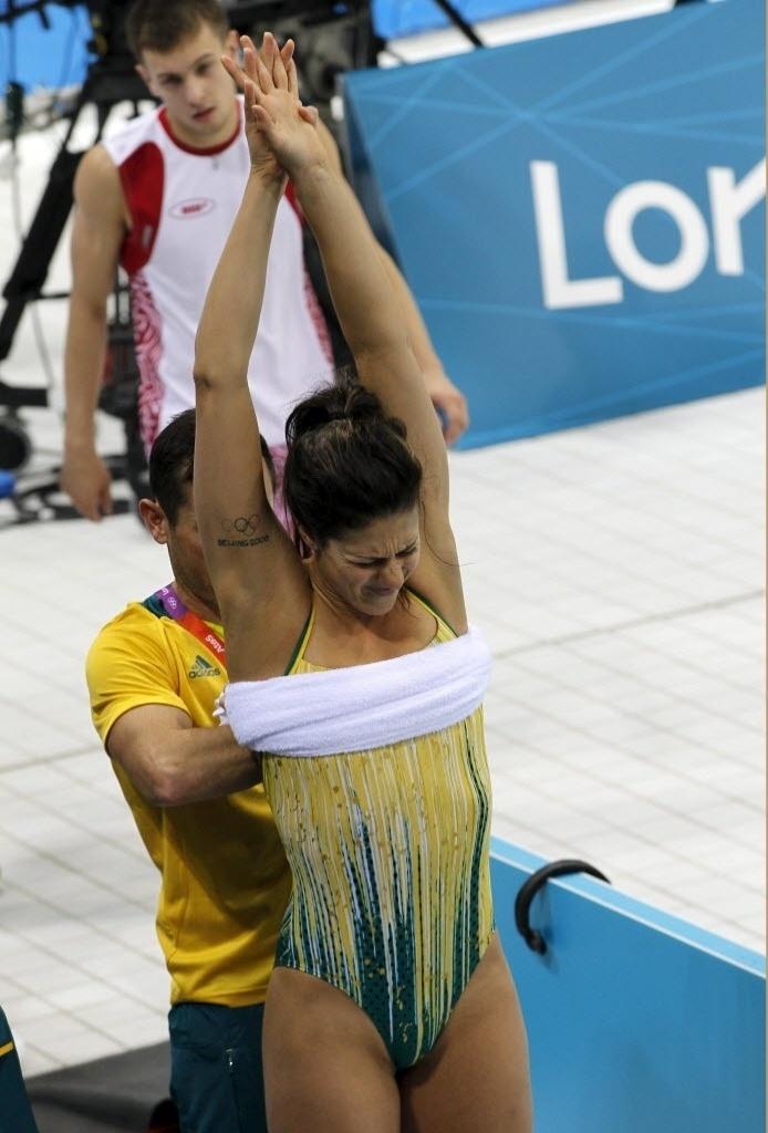 Stephanie Rice faz cara de dor enquanto seu técnico a aperta com uma toalha, após treinos em Londres