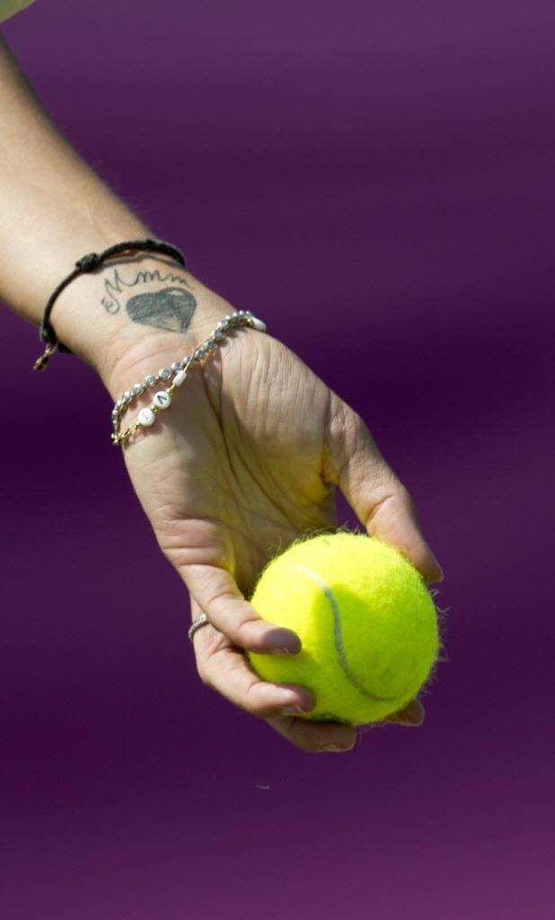 Tenista exibe um coração tatuado no pulso, enquanto se prepara para saque em treino