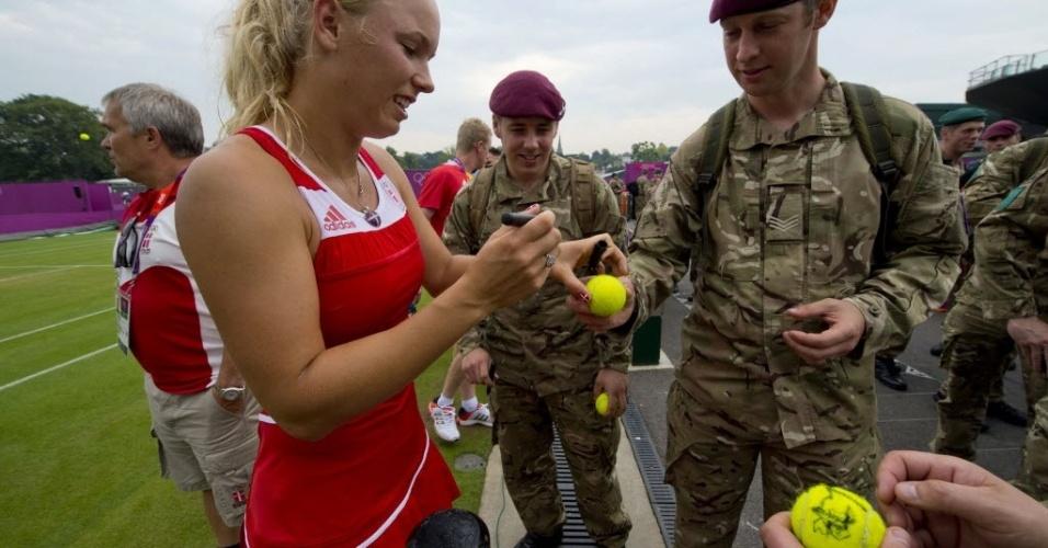 A dinamarquesa Caroline Wozniacki dá autógrafos para soldados durante treino em Wimbledon (27/07/2012)