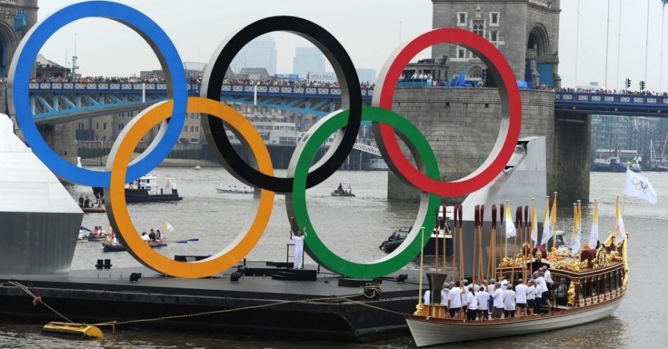Amber Charles segura tocha olímpica em arcos flutuantes no rio Tâmisa, no último dia do revezamento da tocha nesta sexta (27)