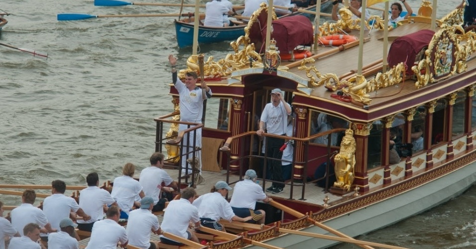 Embarcação real Gloriana carrega chama olímpica ao pelo rio Tâmisa, no último dia do revezamento da tocha nesta sexta (27)