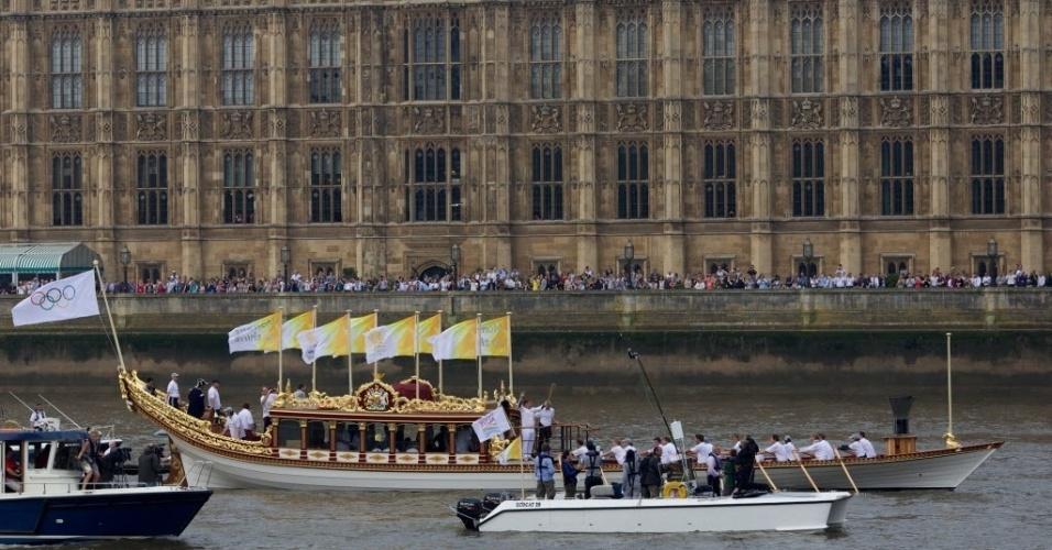 Embarcação real Gloriana passa em frente ao Parlamento com a chama olímpica, no último dia do revezamento da tocha nesta sexta (27)