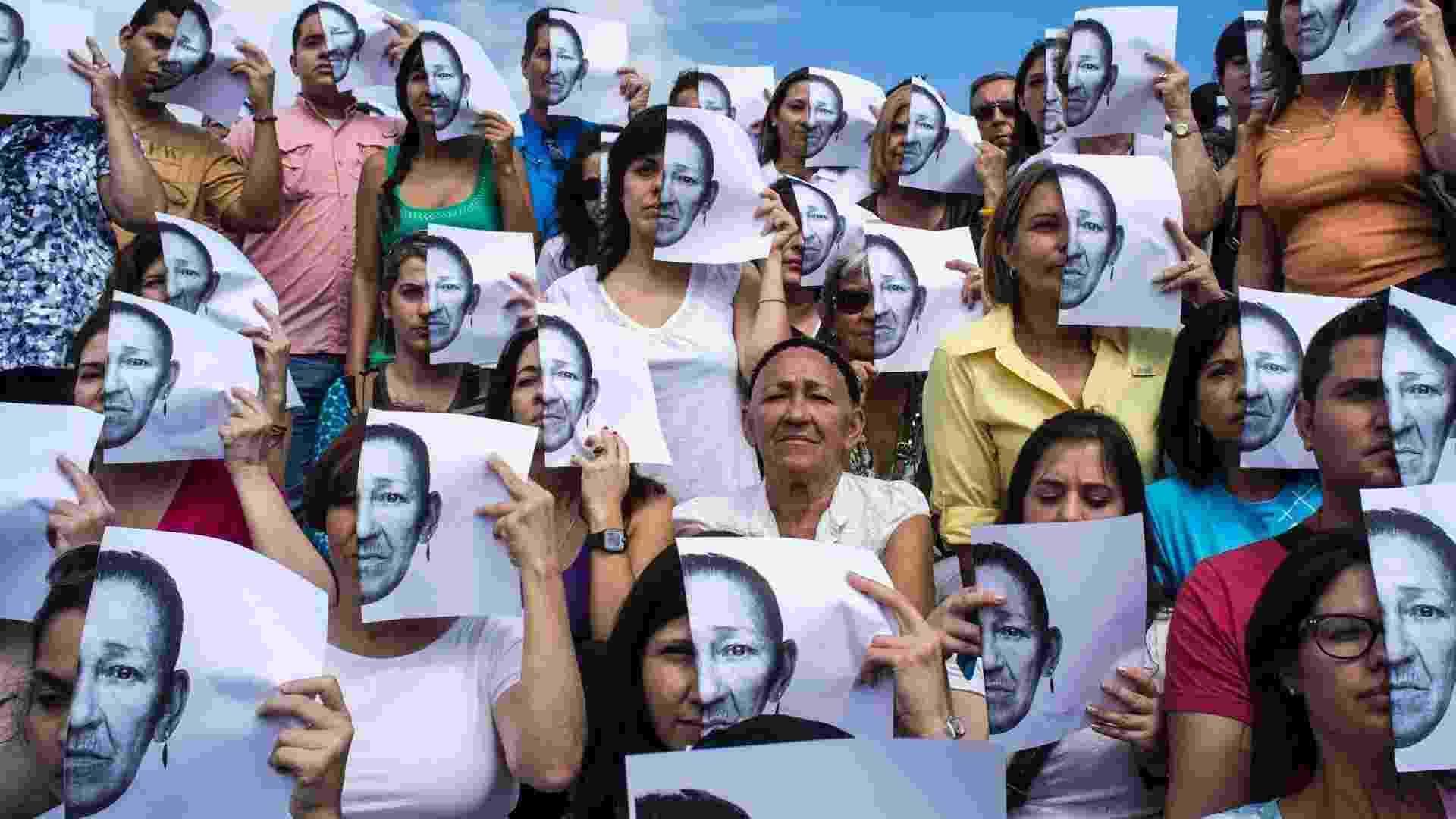 """28.jul.2012 - Maria Delgado, no centro da imagem, perdeu 3 crianças vítimas de violência. Ela posa ao lado de voluntários, neste sábado (28), que seguram uma foto dela na frente do rosto em protesto, na Venezuela. A manifestação faz parte de um projeto chamado """"Esperança"""" que pede a paz por meio da arte - Marco Bello/Reuters"""