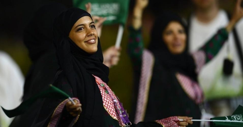 De burca, integrante da delegação da Arábia Saudita carrega bandeiras do país no desfile de abertura