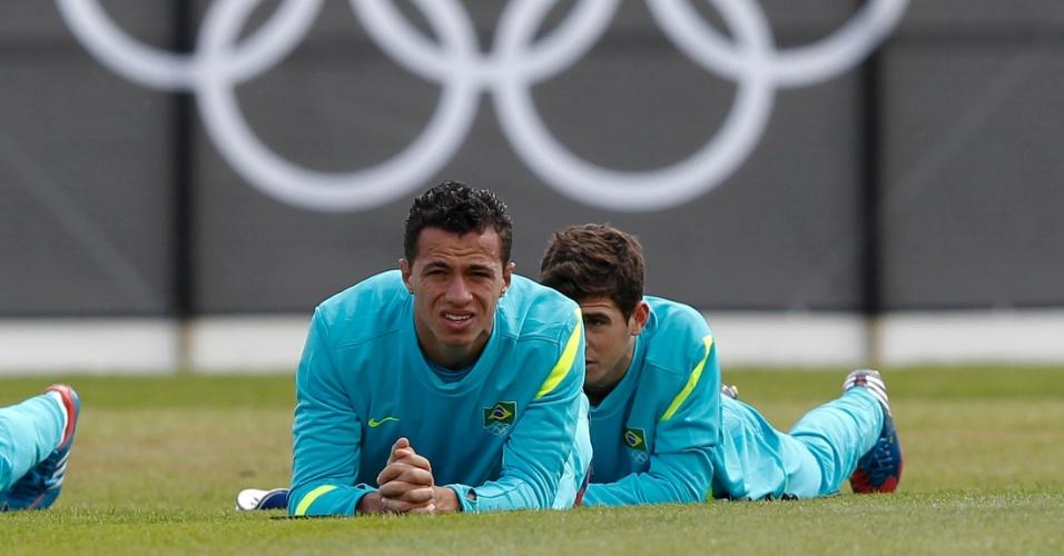 Leandro Damião (e) e Oscar ficam deitados no gramado durante treino da seleção brasileira masculina de futebol (28/07/2012)