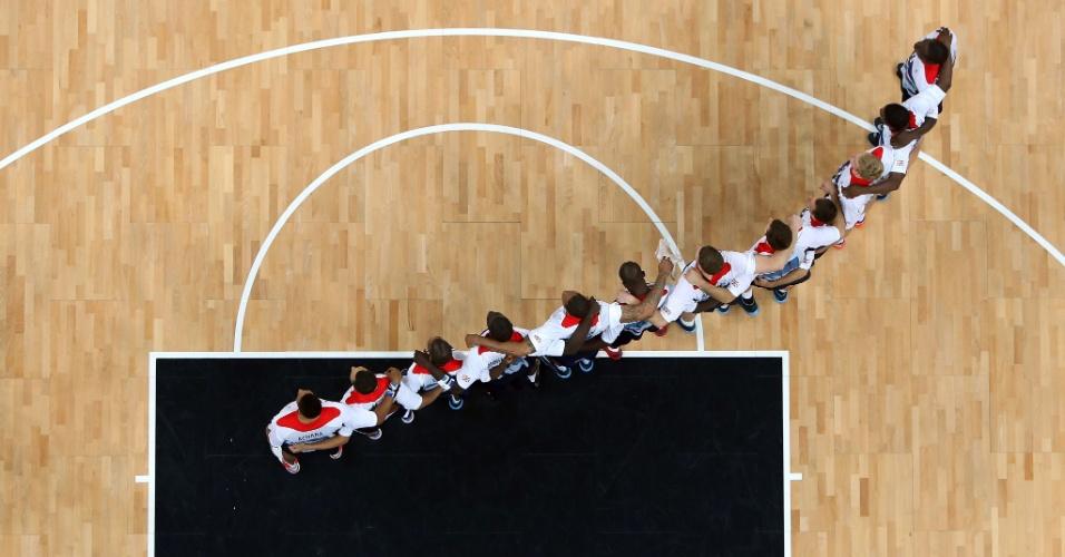 Abraçados, jogadores do Reino Unido aguardam o início da partida de basquete contra a Rússia (29/07/2012)