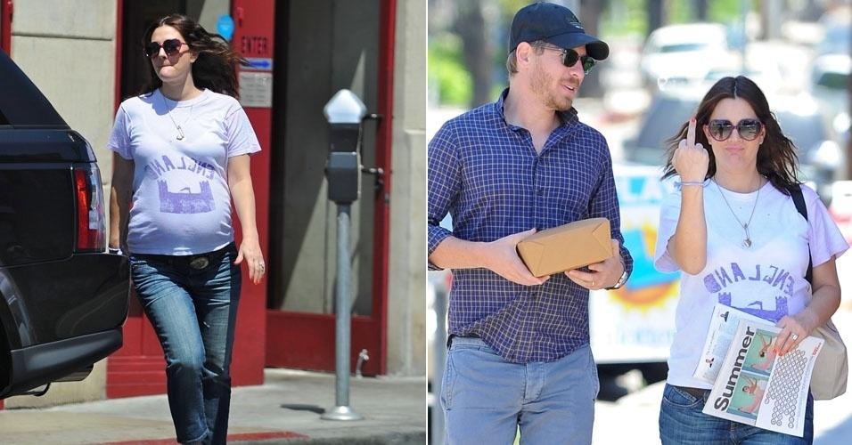 Acompanhada do marido, a gravidíssima Drew Barrymore mostra o dedo para um paparazzi que a seguia em Los Angeles (29/7/12)