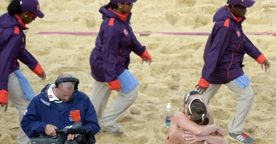 """As britânicas Zara Dampney e Shauna Mullin comemoram, enquanto os voluntários passam """"cobertos"""" até o pescoço"""