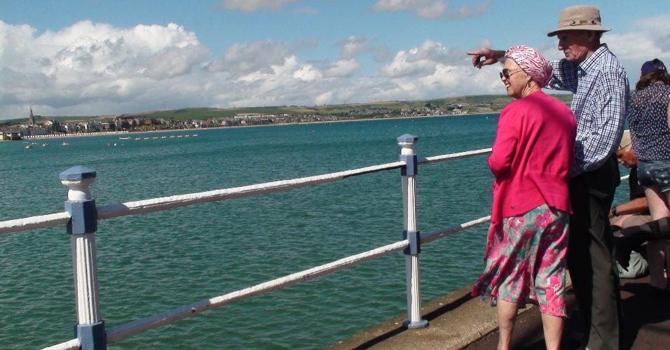 Casal de idosos observam o mar na praia de Weymouth, uma das sedes do iatismo olímpico