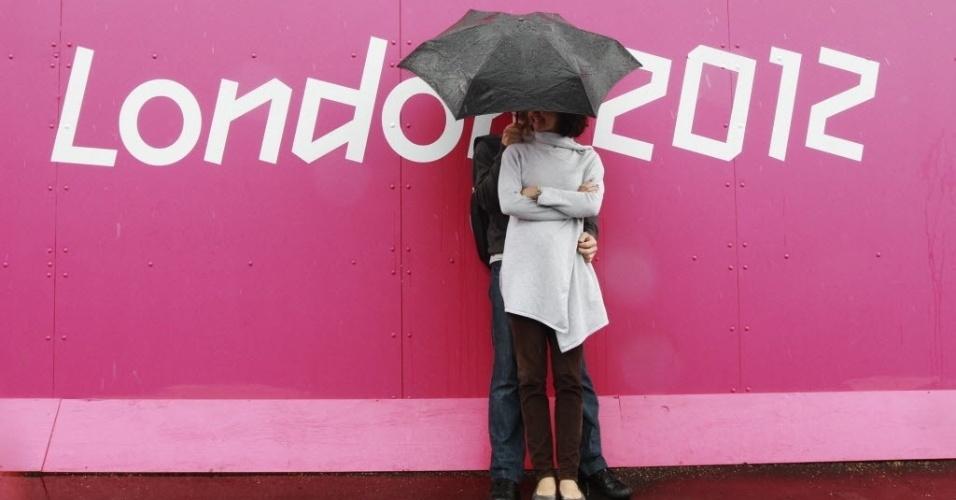 Casal não se incomoda com a chuva e se acomoda sob guarda-chuva em clima romântico