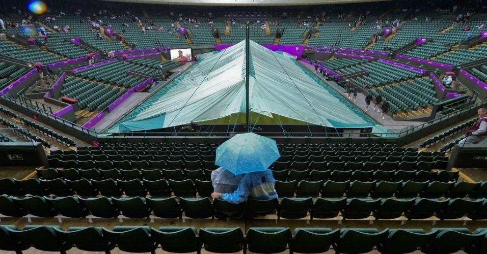 Casal se protege debaixo de um guarda-chuva enquanto a quadra é coberta antes da estreia do sérvio Novak Djokovic nas Olimpíadas de Londres