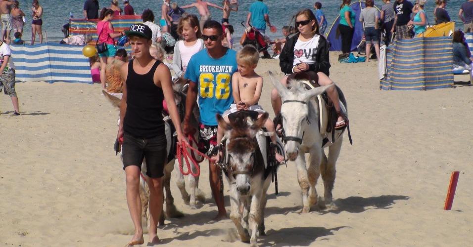 Cena típica das praias inglesas: crianças passeiam em burros alugados pelas areias de Weymouth, uma das sedes dos velejadores olímpicos