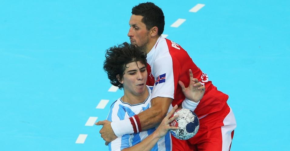 Diego Esteban, da Argentina, é agarrado por jogador islandês em partida disputada neste domingo (29/07)