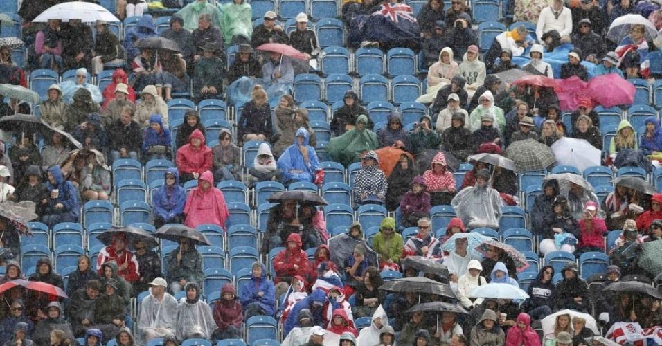 Espectadores tem de se proteger da chuva durante a disputa do hipismo nos Jogos de Londres