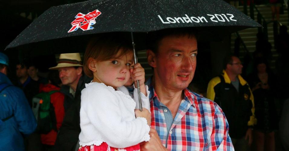 Garotinha e o pai se protegem com um gurda-chuva durante jogo de tênis olímpico em Wimbledon (29/07/2012)