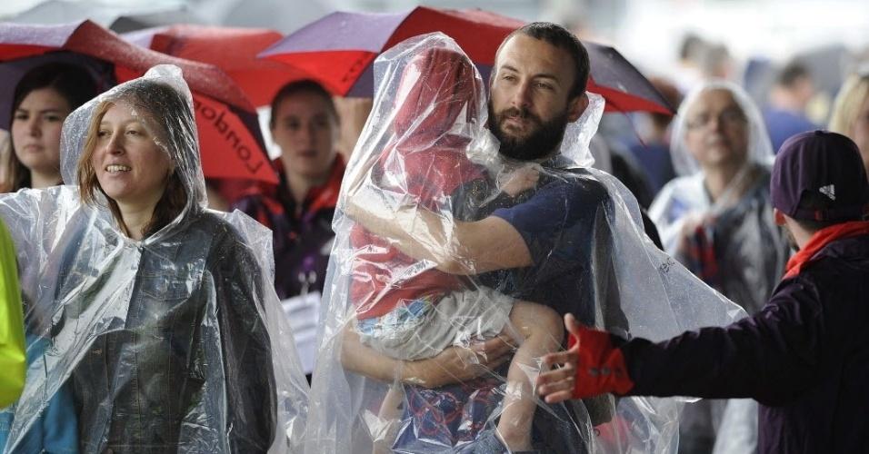 Garotinho é carregado vestindo capa de chuva em dia cinzento em Londres