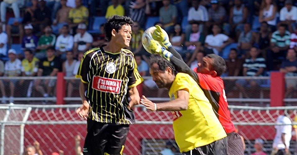 Goleiro do Ajax (preto) sai do gol para impedir o gol do Ouro Preto (amarelo)