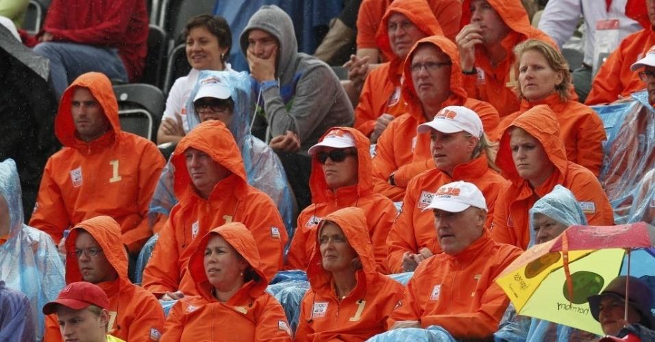 Grupo de torcedores vestidos de laranja se protege da chuva durante partida do hóquei na grama