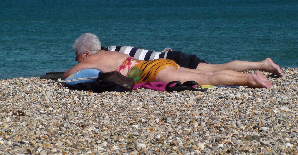 Idosa toma sol entre os seixos da praia de Weymouth, cidade à beira do canal da Mancha que recebe o iatismo olímpico