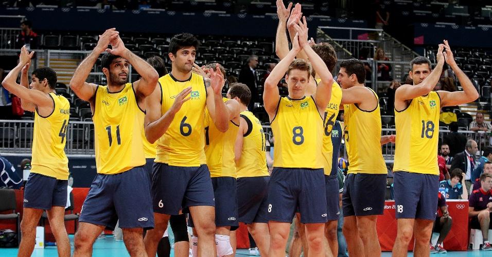 Jogadores da seleção brasileira de vôlei aplaudem a torcida britânica após a vitória sobre a Tunísia