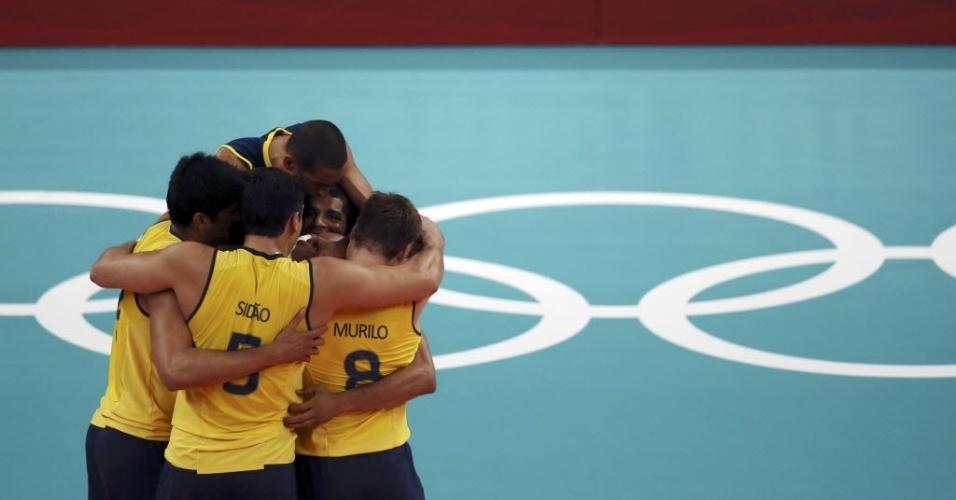 Jogadores da seleção brasileira de vôlei se abraçam para comemorar ponto na vitória sobre a Tunísia