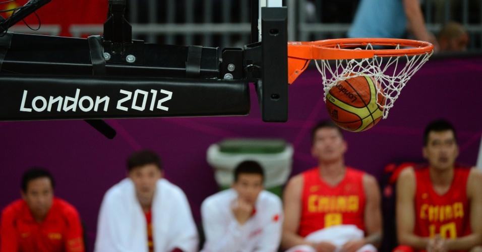 Jogadores da seleção chinesa observam bola caindo na cesta em jogo contra a China