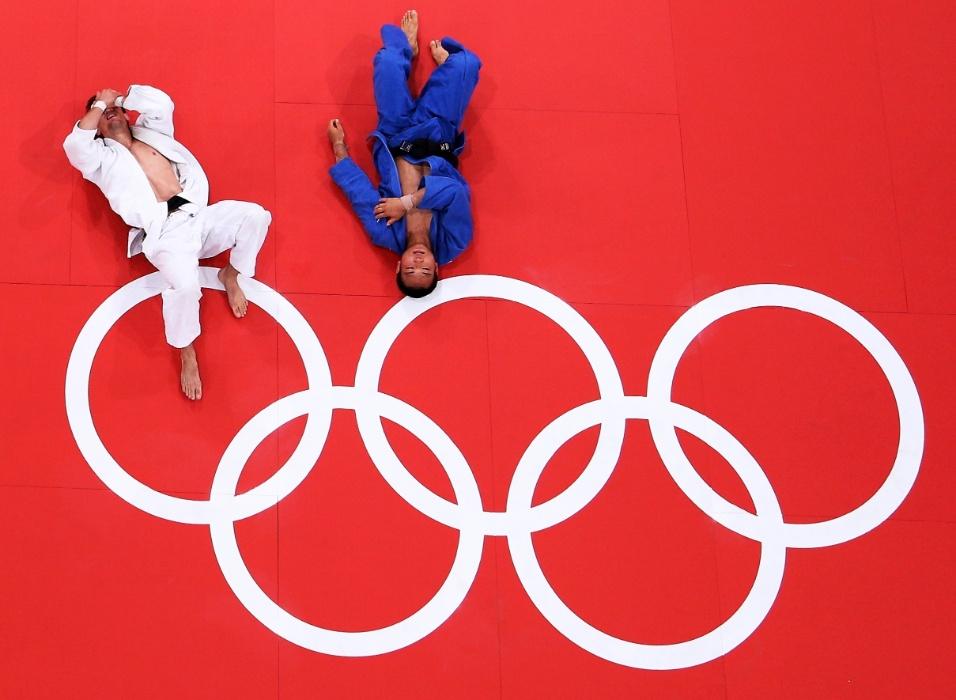 Judocas Pawel Zagrodnik (e) e Masashi Ebinuma ficam deitados no tatame em luta do judô masculino categoria até 66 kg (29/07/2012)
